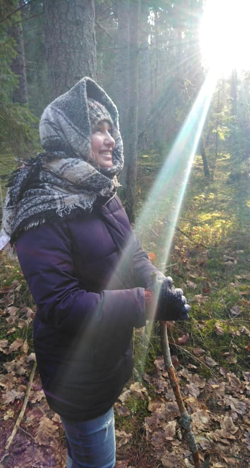 A hiker all bundled up to stay warm on an autumn hike with sun rays coming across the frame