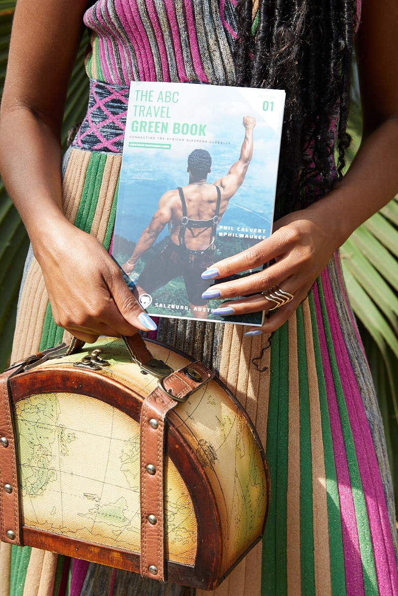 The ABC Travel Greenbook by Martinique Lewis, Marty holds the book and a bag in her hands