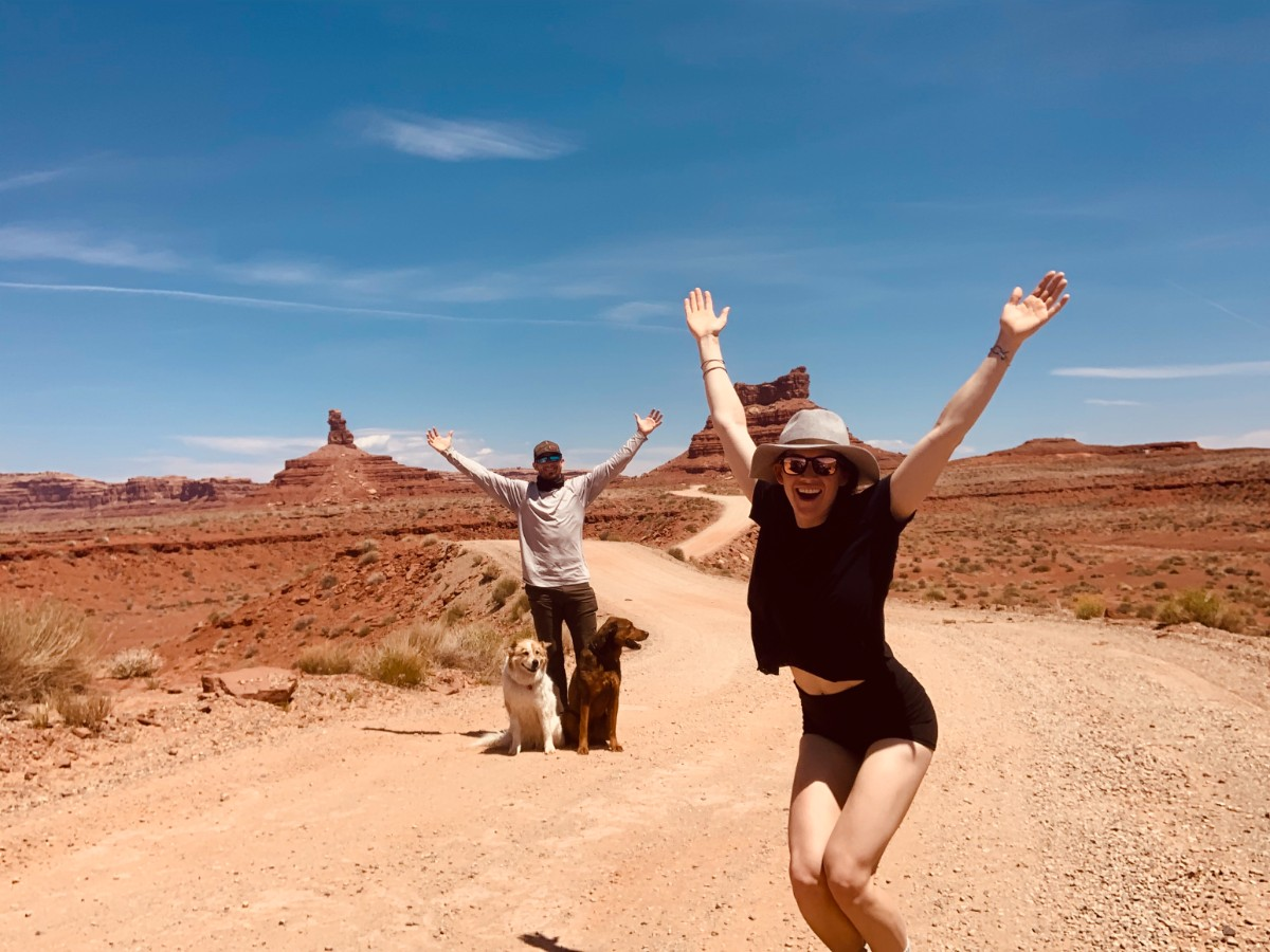 Two joyful people posing with arms outstretched overhead, with two dogs, all seemingly in the middle of a large desert