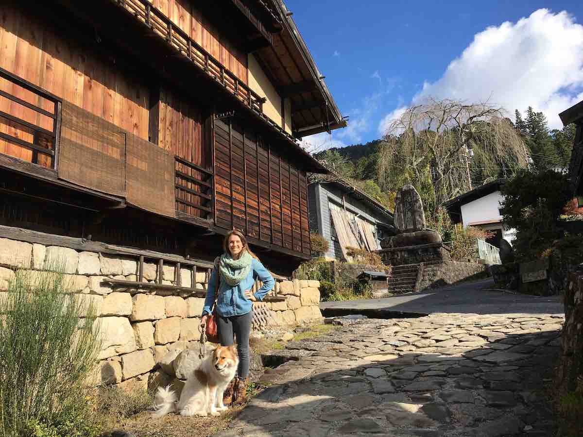 Shelby Dziwulski of Authenteco Travel and her dog in a post town in Japan from Wanderful