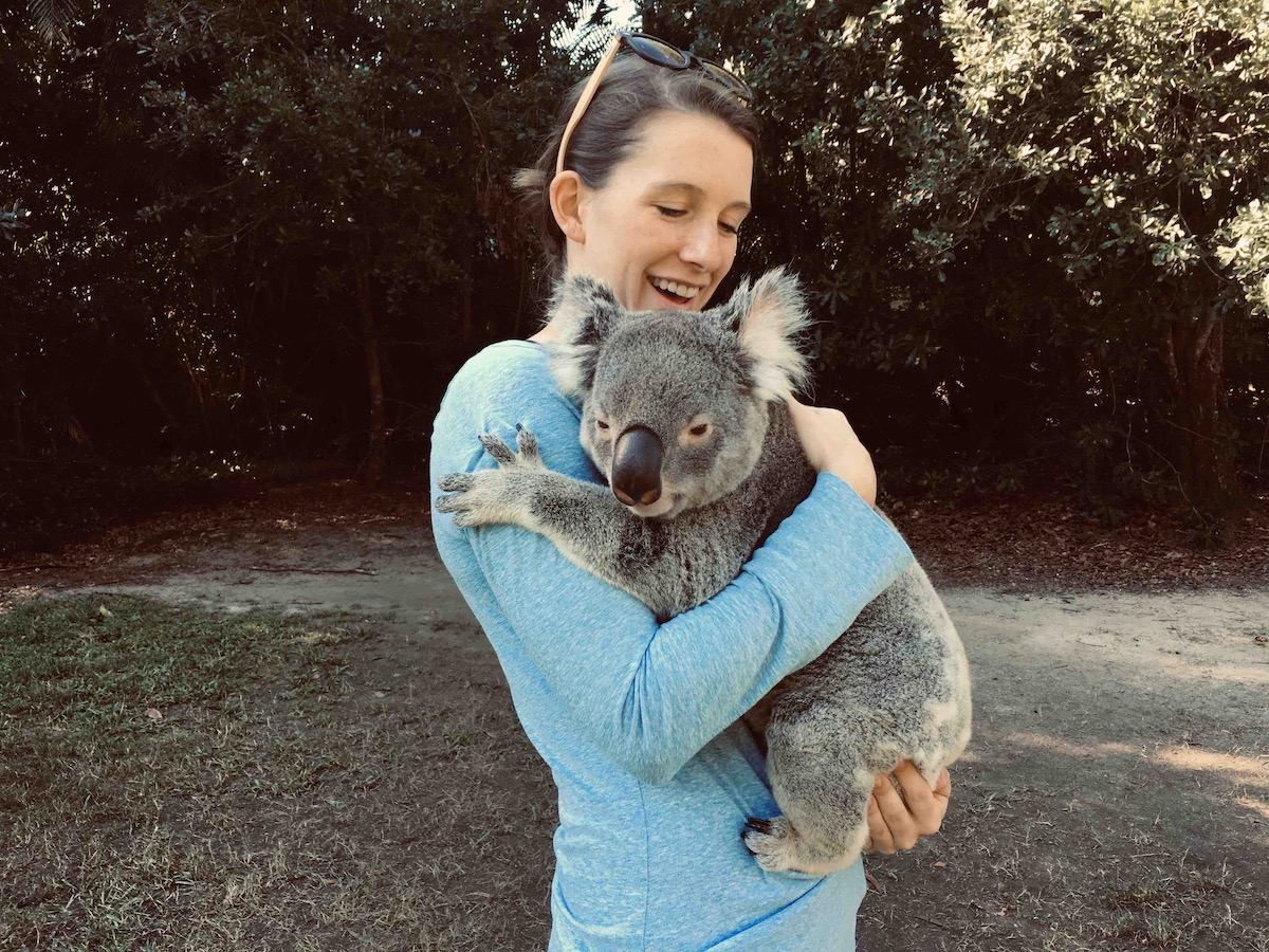 Shelby Dziwulski of Authenteco Travel is pictured in blue hugging a koala from Wanderful