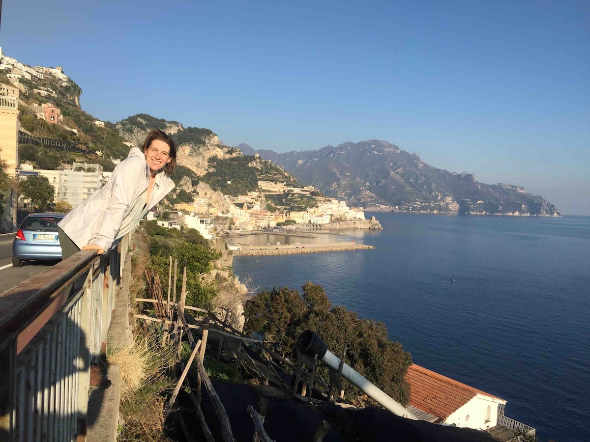 Shelby Dziwulski of Authenteco Travel pictured leaning over a railing near the Italian shoreline, Wanderful