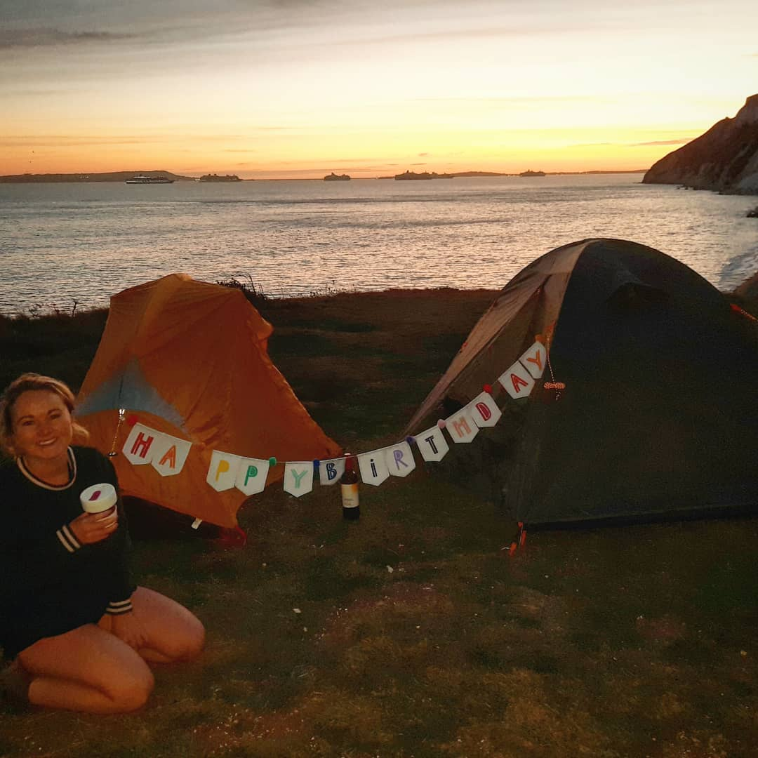Anna Richards wild camping in the UK with a Happy Birthday sign strung across the tent
