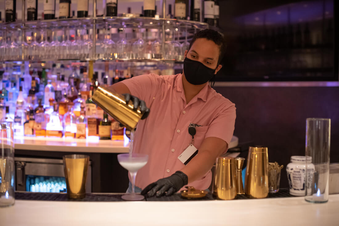 A bartender wearing a facemask and gloves pours a cocktail at the bar at Hotel Zena in DC