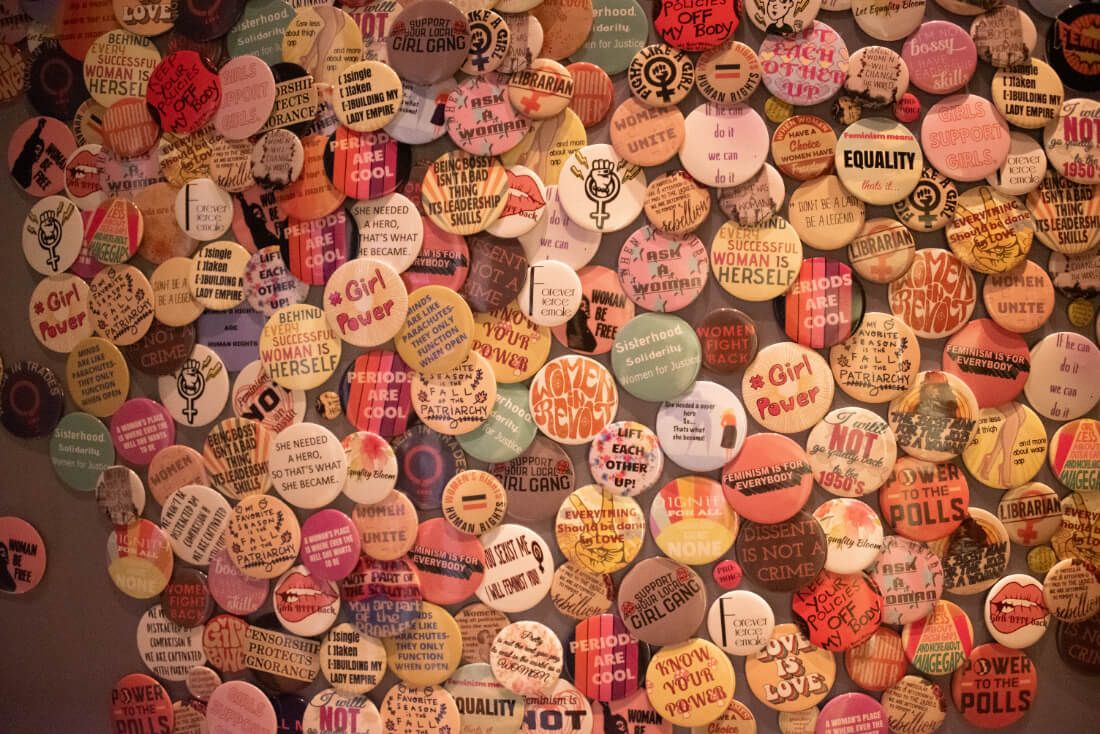Table covered in small pins with feminist statements at Hotel Zena in Washington DC