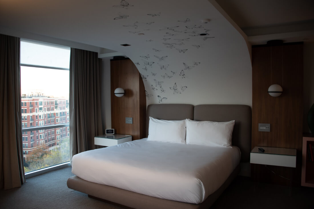 Hotel room at Hotel Zena in DC with an arched ceiling covered in butterflies over the bed
