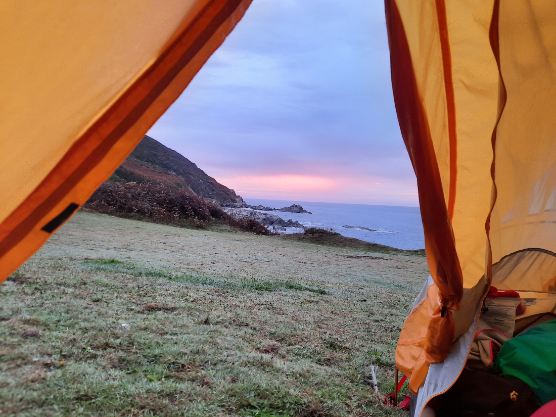 View through an open tent of a sunset over the sea