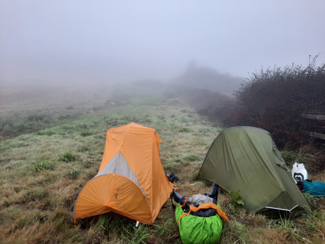 Wild camping in the UK - tents on a grassy field in the fog