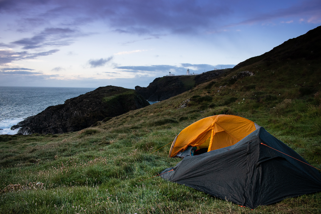 Two small tents set up on a green hillside by the sea