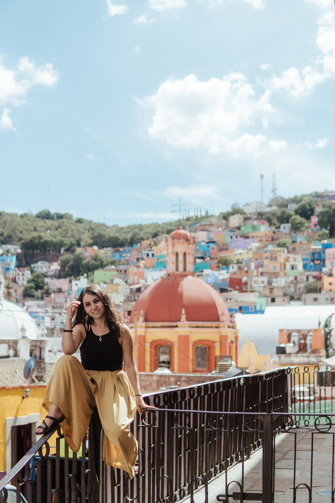 Stacey Valle sitting on a metal railing with a backdrop of colorful houses on the hillside behind her