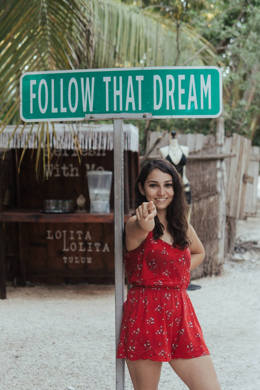 Stacey Valle pointing at the camera while standing under a sign that says Follow that dream