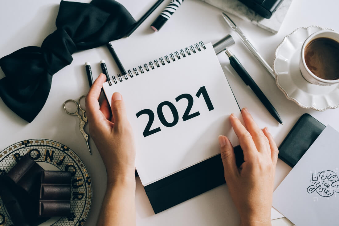 Hands holding a 2021 calendar for goal setting for the new year