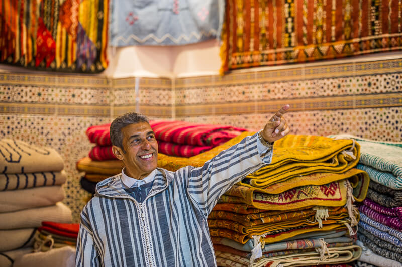 Man pointing at traditional Moroccan woven rugs