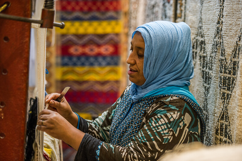 Woman weaving a rug in Morocco
