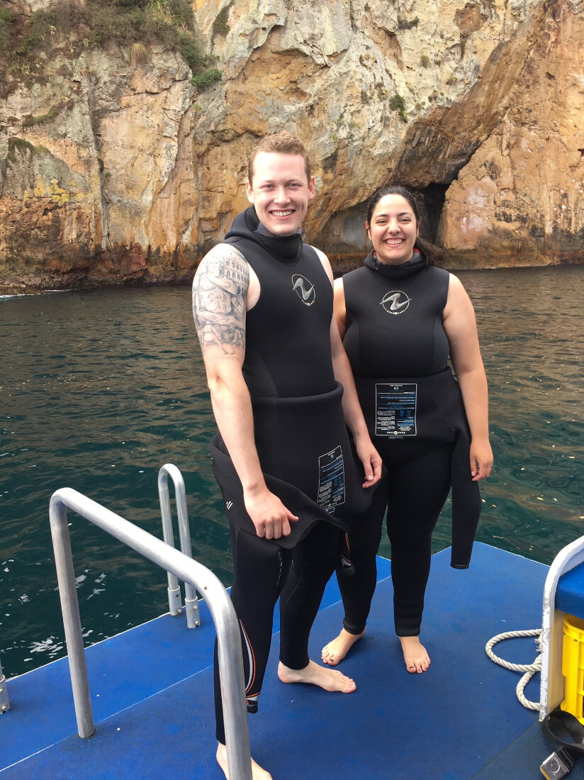 McKenna Hurd and her husband in wetsuits ready for their first ocean scuba diving experience in New Zealand