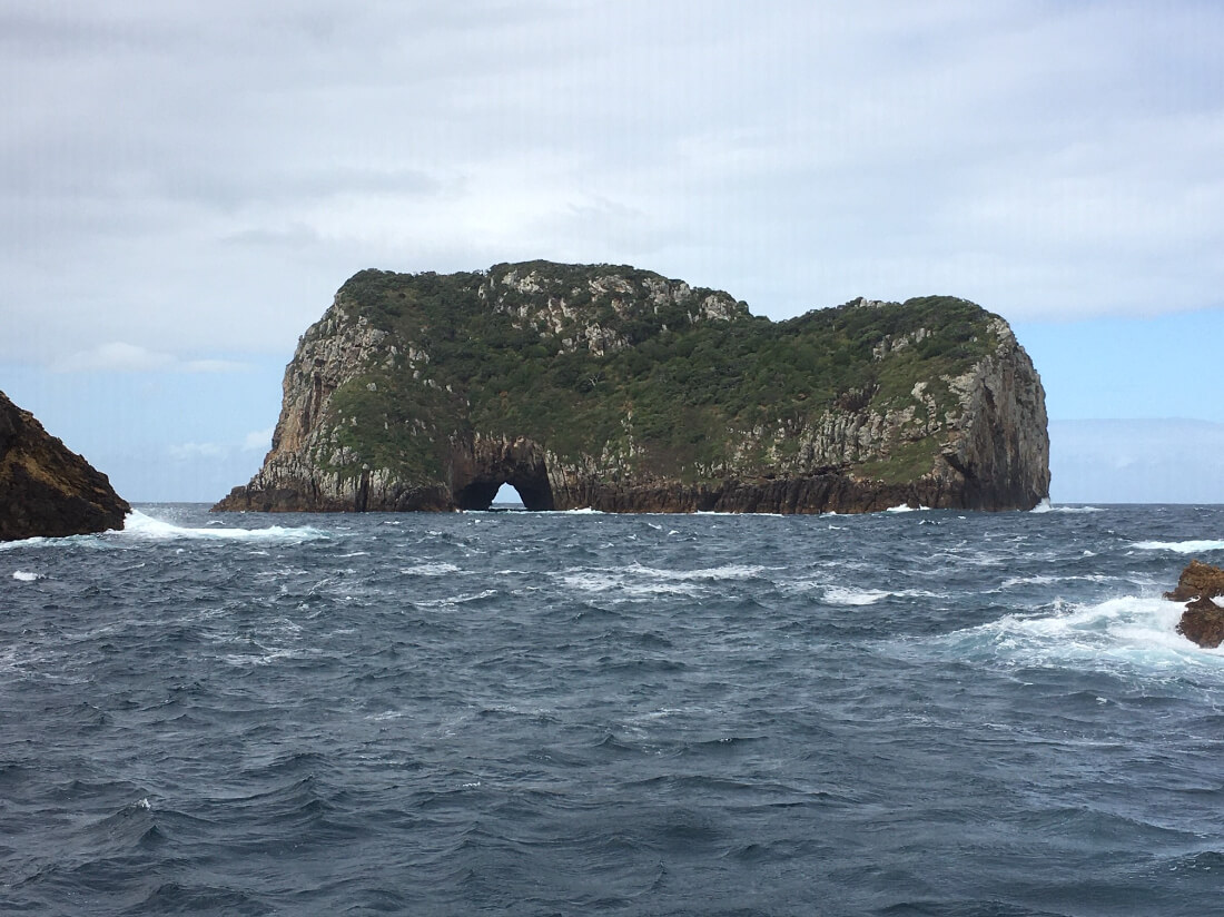 A photo taken at sea level looking at a small island rising up