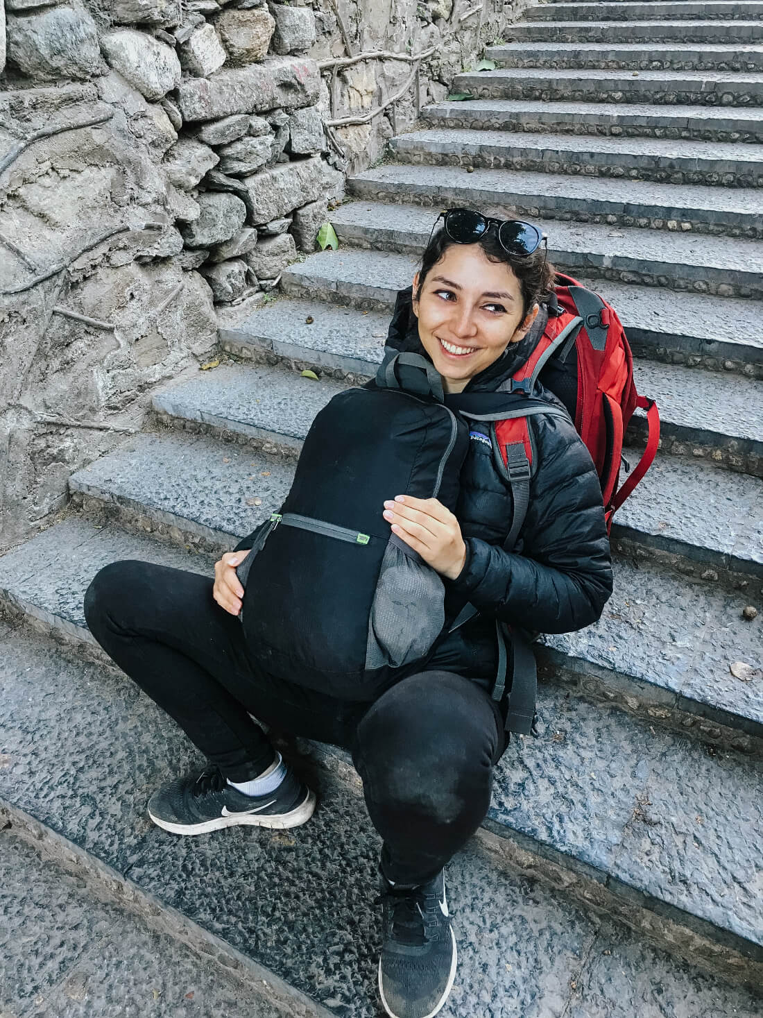 Stacey Valle with a large backpack and another smaller backpack on her front, sitting on a staircase looking exhausted but smiling