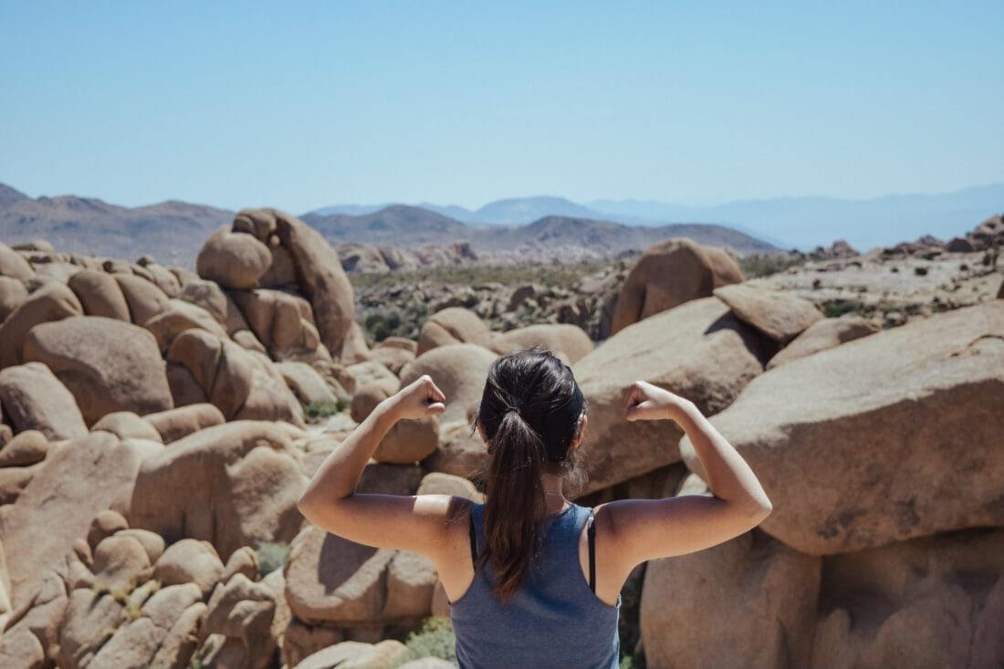 Woman standing before a desert landscape with her back to the camera raising her arms in a strong pose