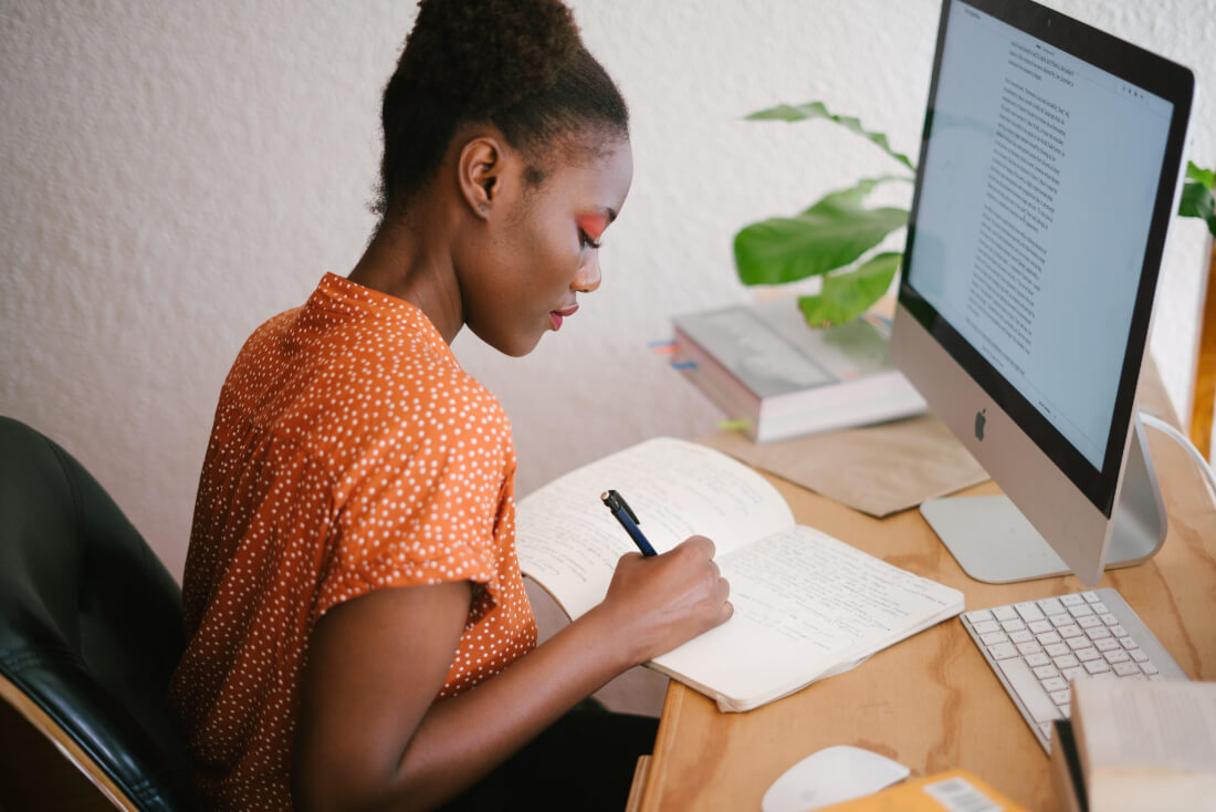 A woman writing in a notebook in front of a desktop computer