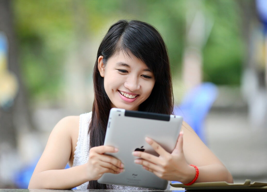 Woman smiling using a tablet