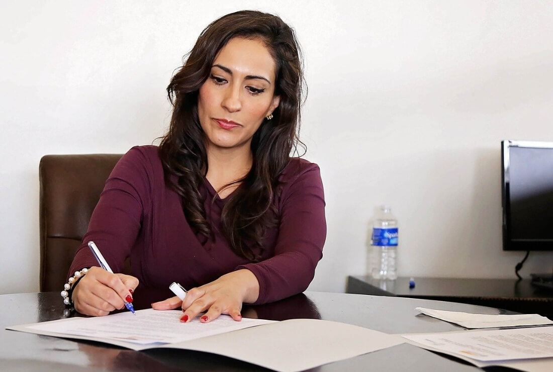 Woman signing documents at an office desk