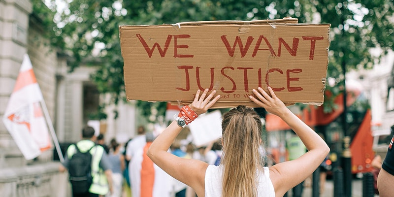 """Woman holding a sign that says """"We want justice"""" for a Wanderful event called """"Allyship in Action: Creators Holding Travel Brands Accountable"""""""