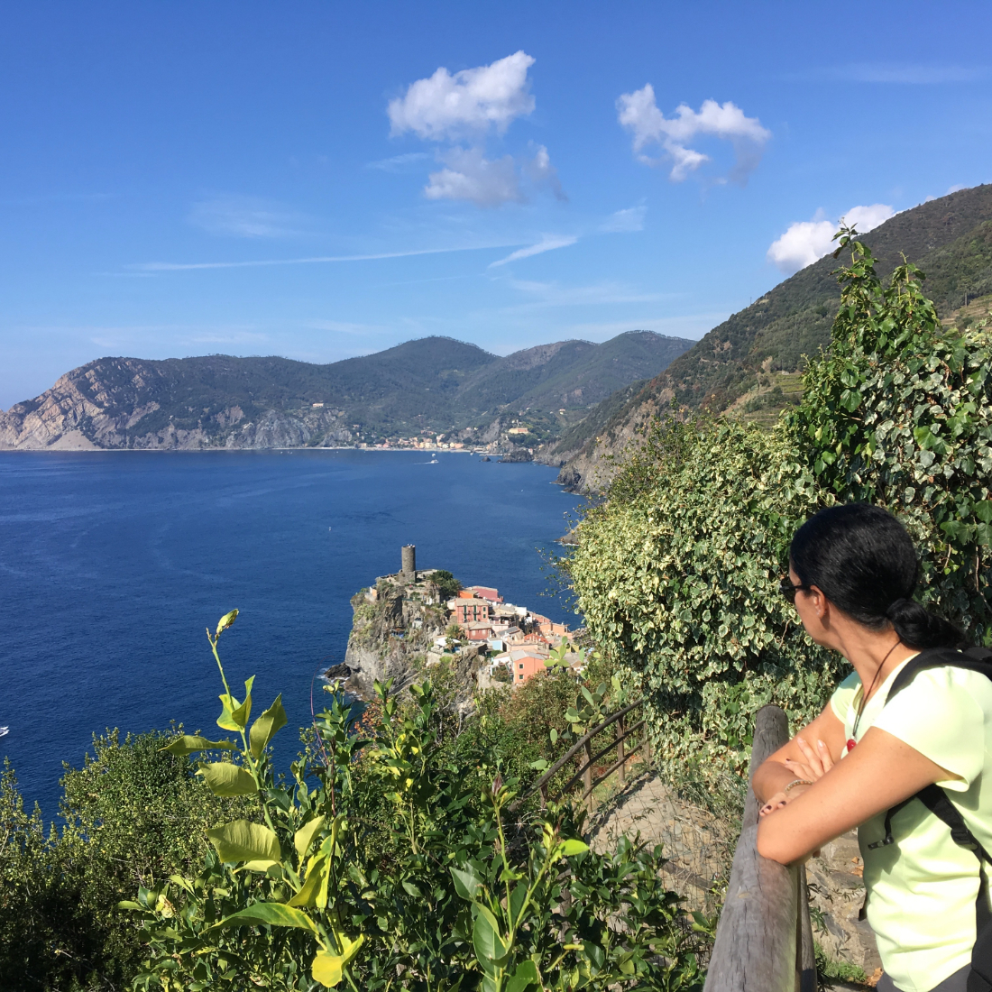 Bright blue sea and sky as a woman looks out from behind a railing along the hiking trail in Cinque Terre Italy