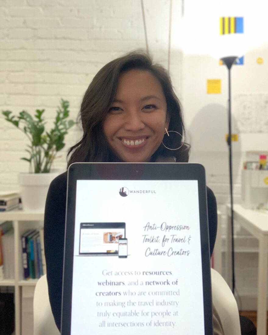 Justine Abigail Yu behind her co-created Anti-Oppression Toolkit on a tablet