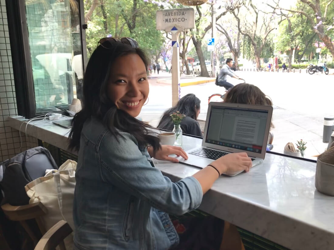 Justine Abigail Yu sitting at her laptop in an open-air bar in a tropical setting