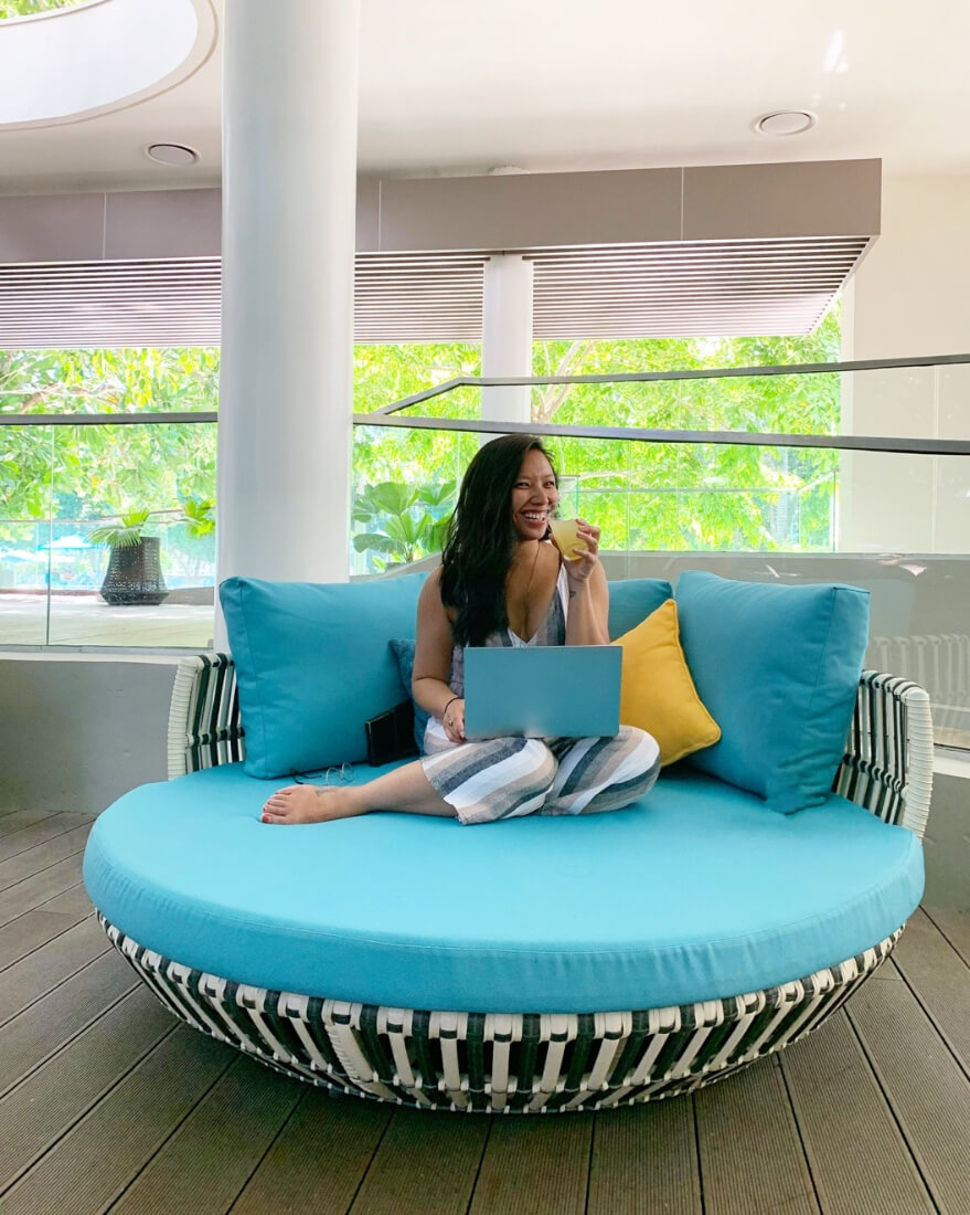 Justine Abigail Yu sitting on a teal round chair holding a tropical juice