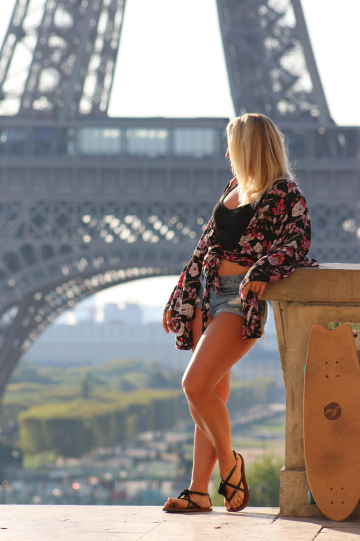 Chel Rogerson leaning against a short wall with the base of the Eiffel Tower in the background