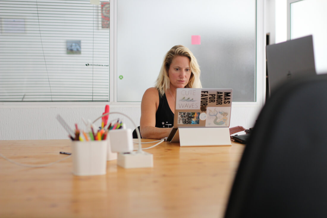 Chel Rogerson at her laptop in a large coworking space with lots of natural light in Fuerteventura