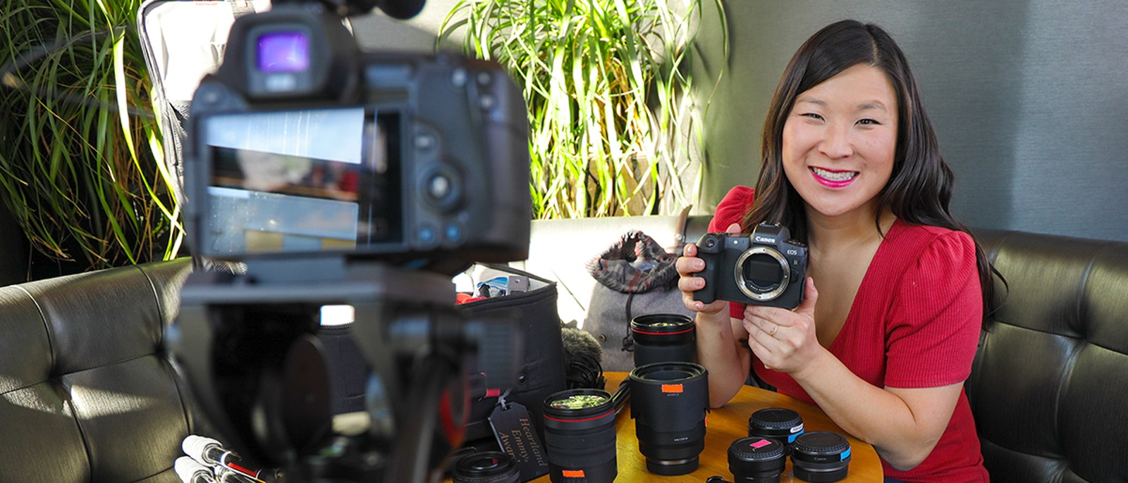 Juliana Broste holding a camera in front of other camera gear | Wanderful membership event