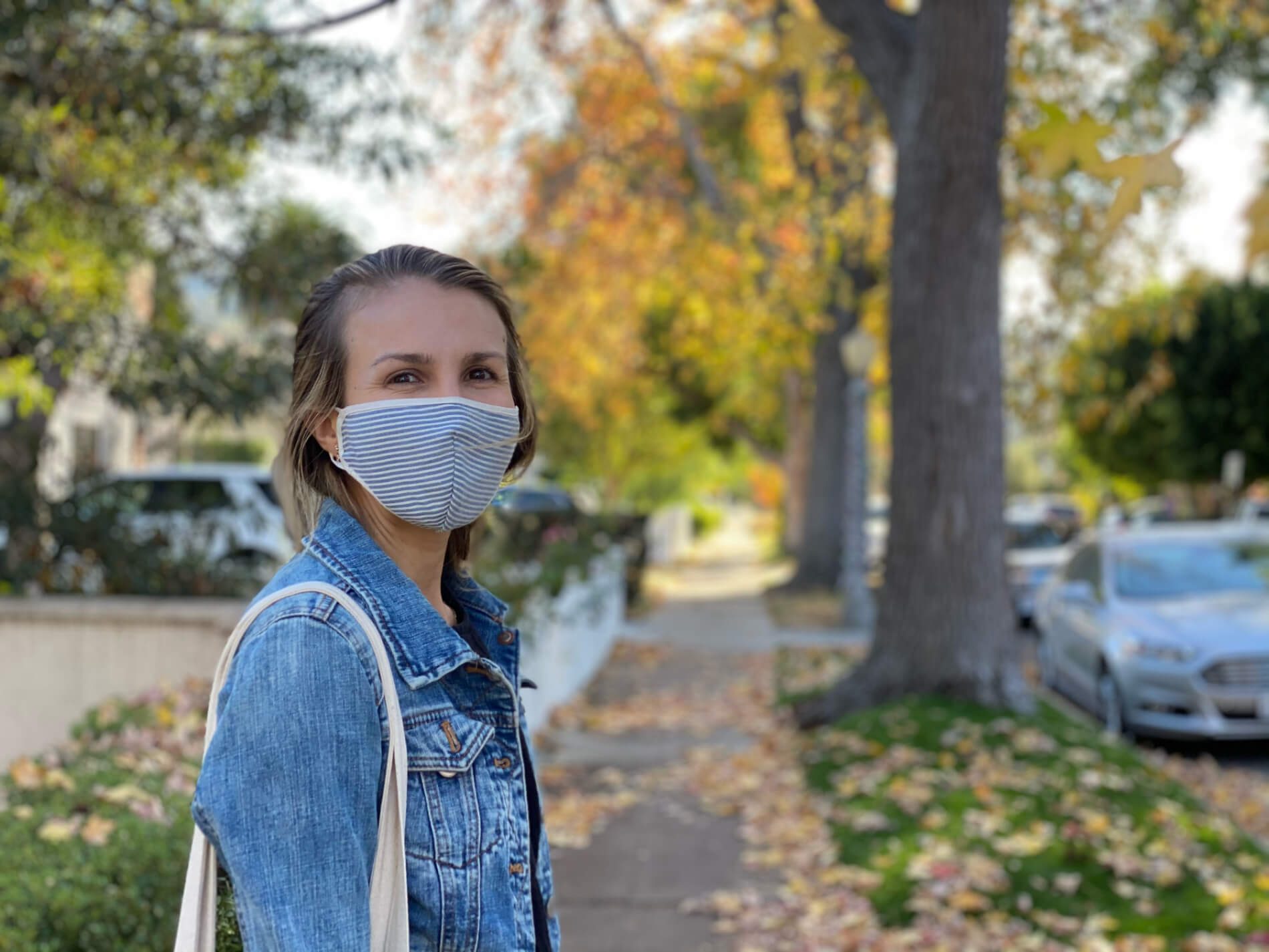 Marika Price wearing a face mask posing on a sidewalk during an autumn walk in quarantine