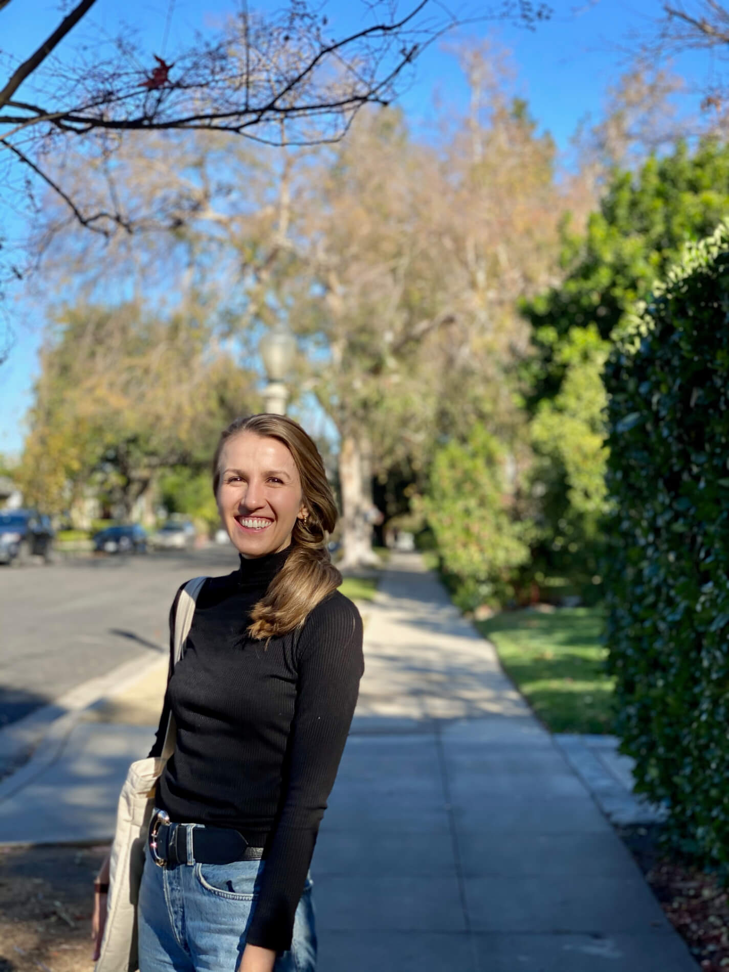 Marika Price posing on a sidewalk on a sunny day walk